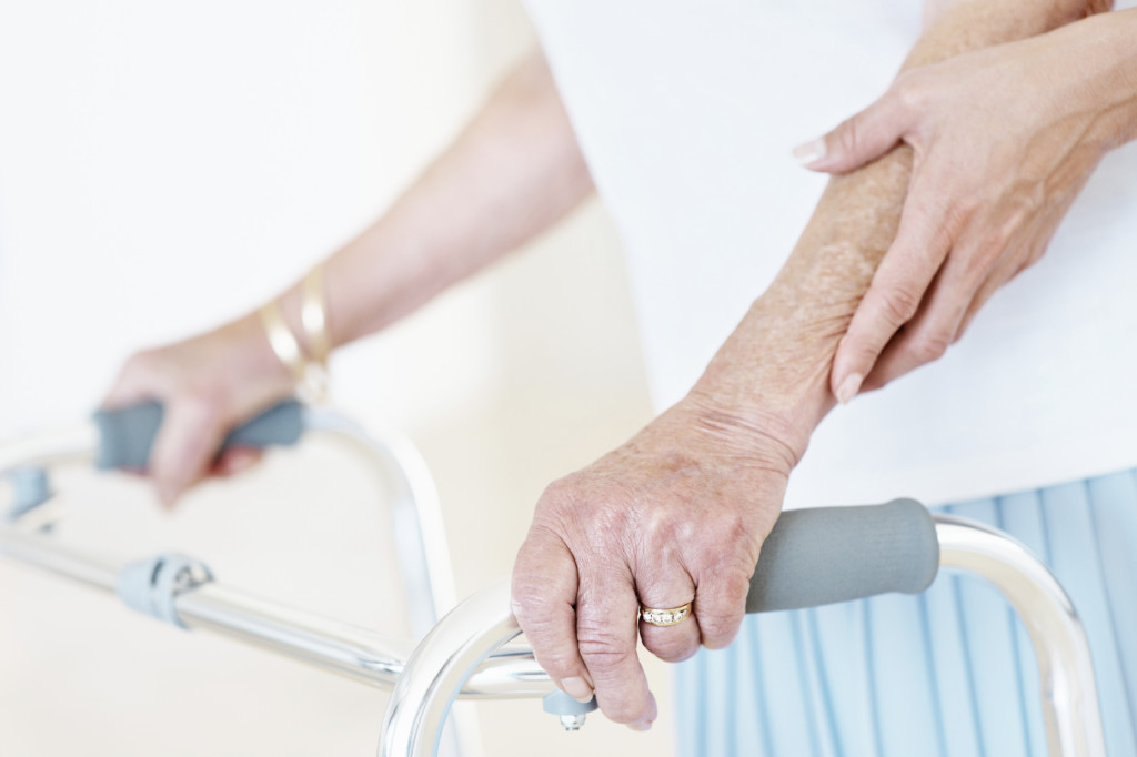A close-up of a young woman's hands and an old lady's hands using a walker as support