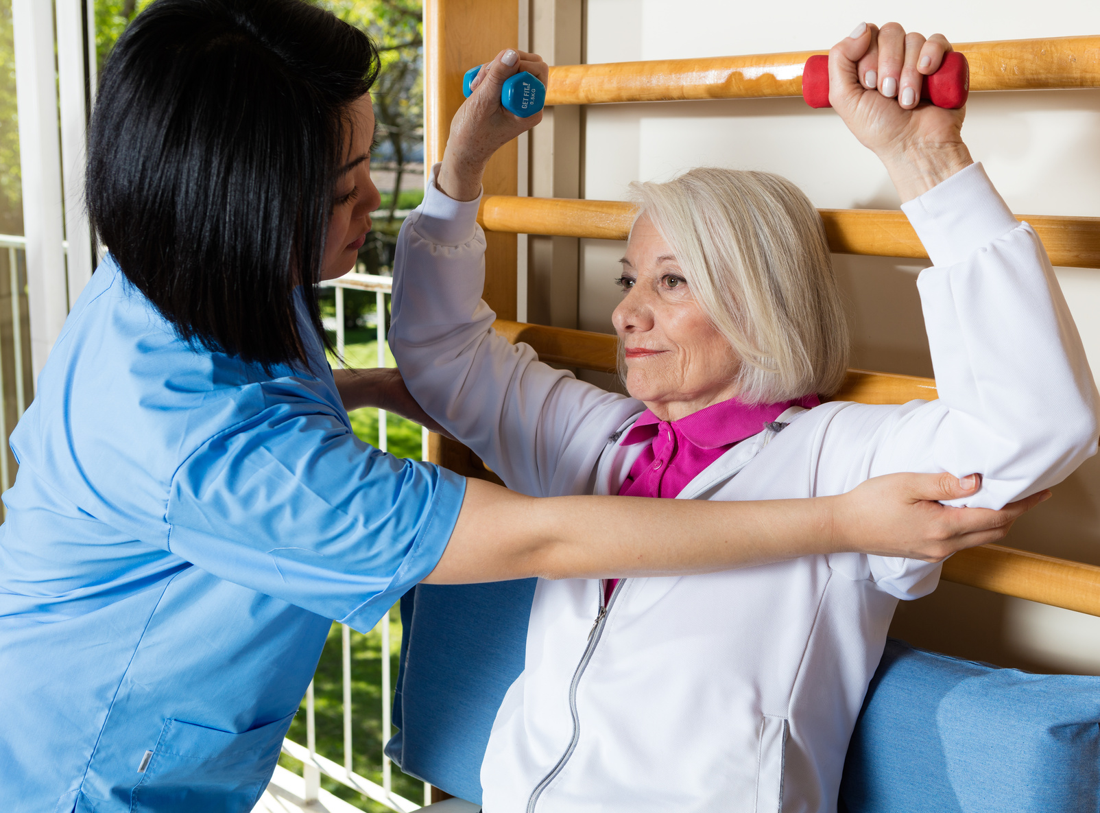 Woman in 60s lifting weighs at hospital gym, helped by nurse.